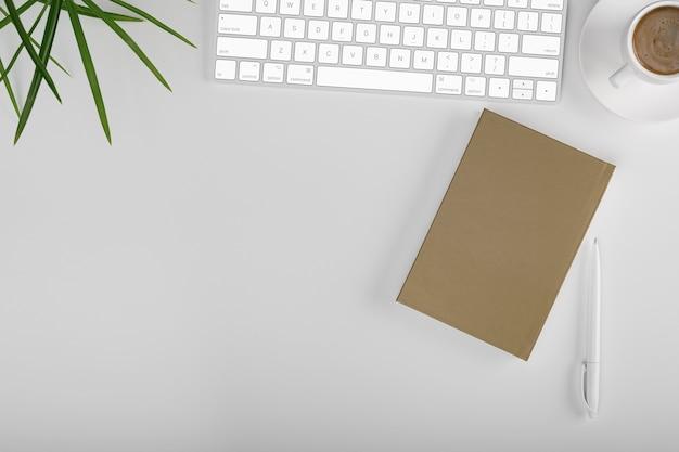 Biurko z widokiem z góry. obszar roboczy z pustym, biurowym, ołówkiem, zielonym liściem i filiżanką kawy na białym tle.