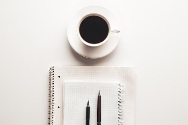 Biurko z zapasami, filiżanką kawy i kwiatkiem. widok z góry z miejscem na kopię