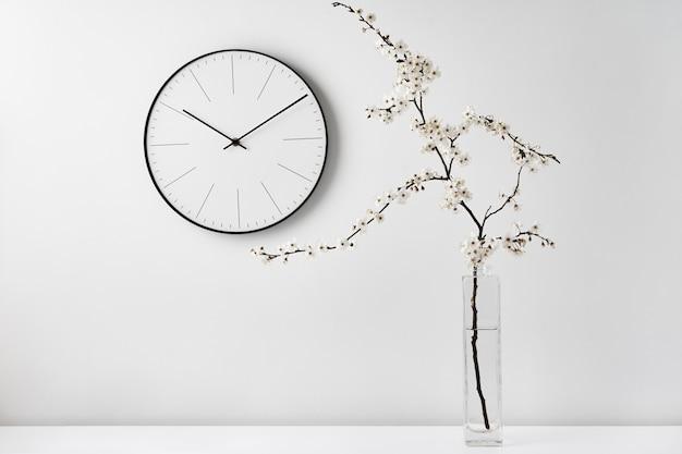 Biurko z zegarem ściennym i gałązką na białym tle. minimalistyczny styl wystroju