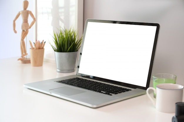 Biuro biurko stół z pustego ekranu laptopem i plakatem