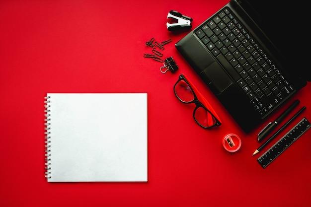 Biuro domowe biurowe miejsce pracy z laptopem notebook biurowy i artykuły papiernicze na czerwonym odwrocie