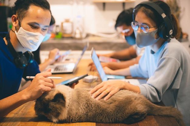 Biuro domowe, praca z domu i zabawa z kotem, noszenie maski na twarz podczas pracy nad utrzymaniem dystansu społecznego podczas covid-19, praca freelancera online, koncepcja stylu życia.