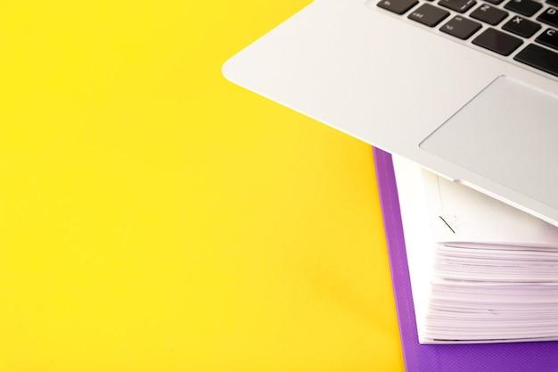 Biuro, folder z dokumentami oczekującymi na weryfikację, laptop na żółtym tle. koncepcja biznesu i edukacji. skopiuj miejsce. selektywne skupienie.
