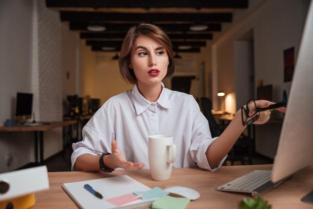 Biuro kobieta pokazuje palec w komputerze. ja