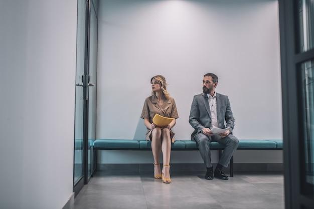 Biuro, koledzy. brodaty mężczyzna w szarym garniturze i młoda kobieta w sukni z dokumentów siedzi patrząc na szklane drzwi na korytarzu biura