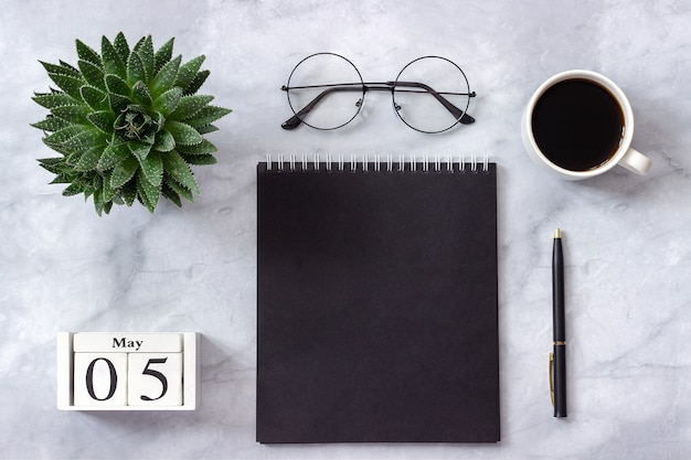 Biuro lub stół domowy, kalendarz 5 maja. czarny notatnik, kawa, soczysty, szklanki na marmurze