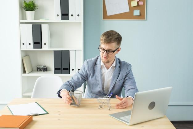 Biuro, ludzie biznesu, przerwa koncepcja - kierownik bawi się wózkiem z supermarketu z zabawkami w biurze podczas pracy.