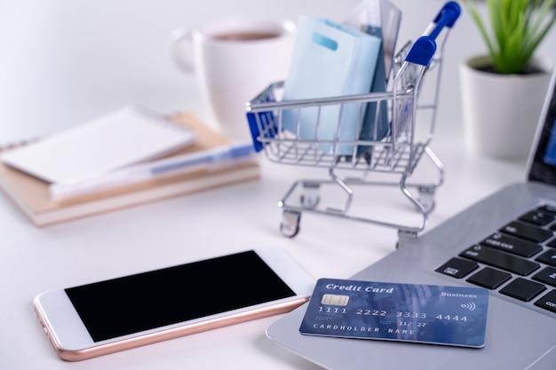 Biuro online płacenie, zakupy w domu, płatności elektroniczne z koncepcją karty kredytowej, laptop na tle białego stołu z wózkiem sklepowym, z bliska.