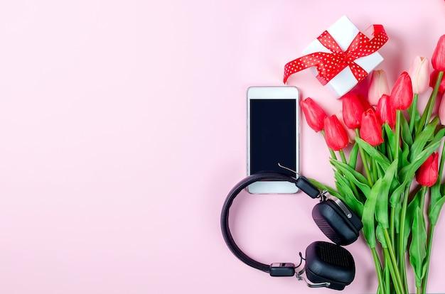 Biuro pracy z czerwonym sercem, pudełko, tulipany, telefon i słuchawki na różowo