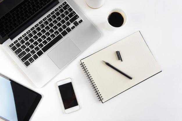 Biuro stół z laptopem, notatnikiem, cyfrową pastylką i smartphone na białym tle ,.