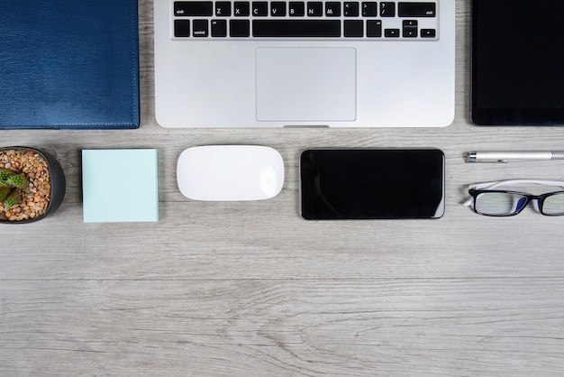Biuro stół z laptopem, notatnikiem, cyfrową pastylką i smartphone na drewnianym backgr ,.