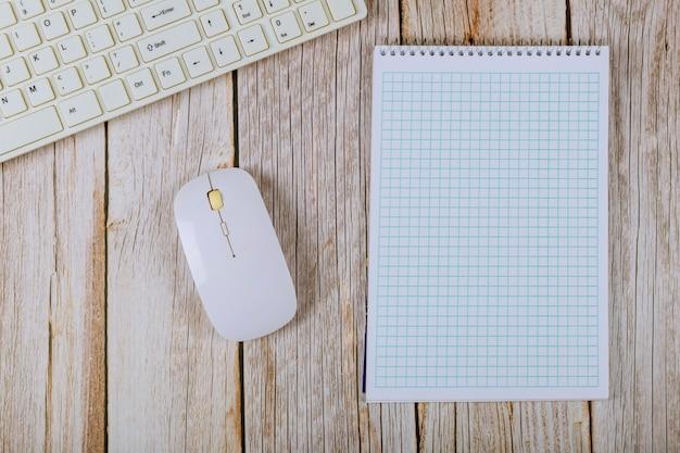 Biuro stół z pustym notatnikiem i klawiaturą na drewnianym stołowym tle.