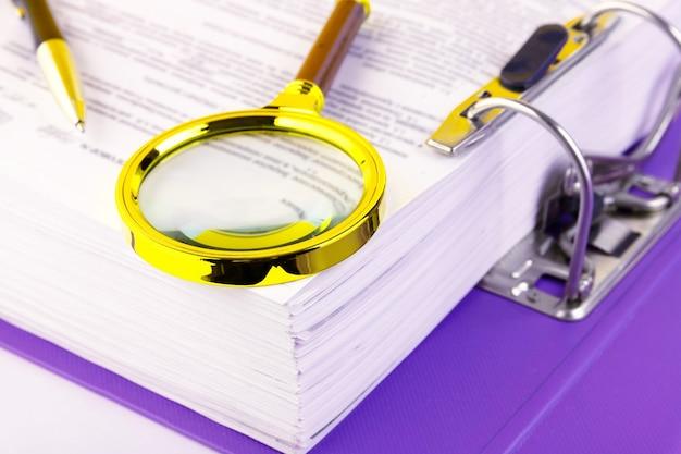 Biuro, teczka z dokumentami oczekującymi na weryfikację, lupa w złotej oprawie. koncepcja biznesu i edukacji. skopiuj miejsce. selektywne skupienie.