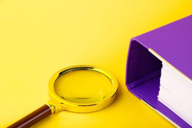 Biuro, teczka z dokumentami oczekującymi na weryfikację, szkło powiększające, na żółtym tle. koncepcja biznesu i edukacji. skopiuj miejsce