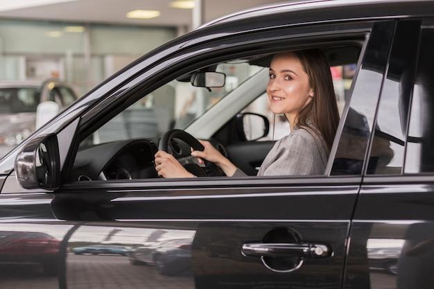 Biuro ubrana kobieta siedzi w samochodzie
