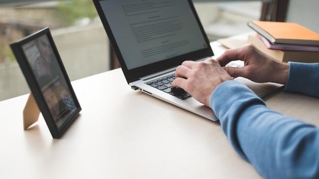 Biuro w miejscu pracy mężczyzna pracujący na laptopie przed oknem w biurze biznesowym