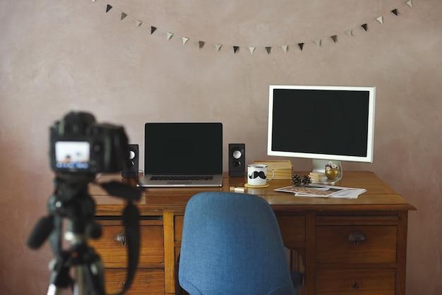Biuro z czarnymi ekranami i aparatem na statywie