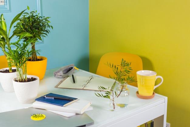 Biuro z jasnymi ścianami. papeteria i kwiaty na stole