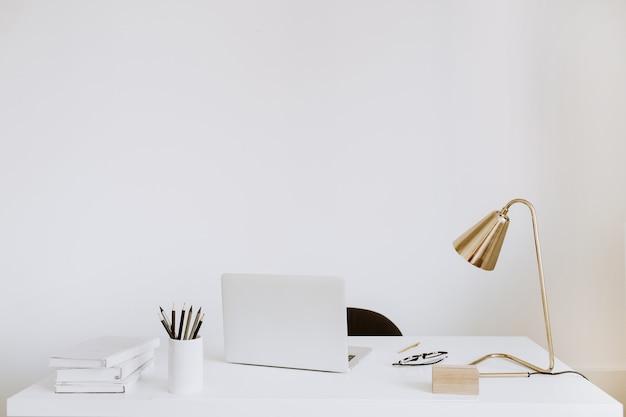 Biuro z laptopem, lampą, notebookami. biały obszar roboczy szafki do pracy.