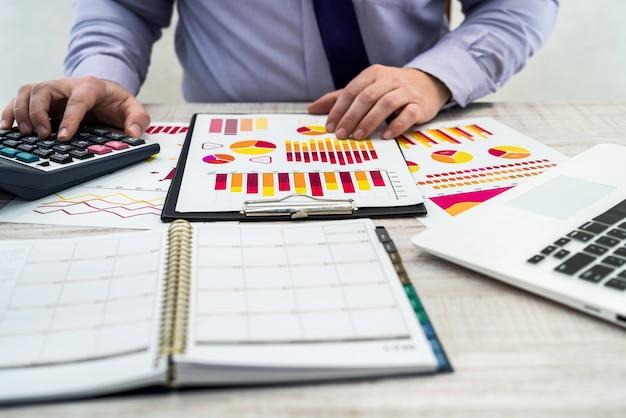 Biuro zawód biznes, technologia, finanse i koncepcja - młody biznesmen z laptopa diagramu wykresu i dokumentów w biurze