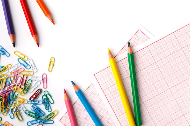 Biurowa klamerka i barwioni ołówki na białym tle