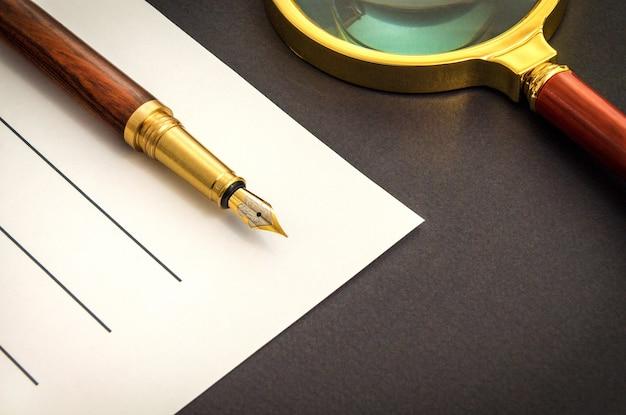 Biurowa martwa natura na czarnym stole z długopisem na kartce i lupą przygotowująca do nagrań