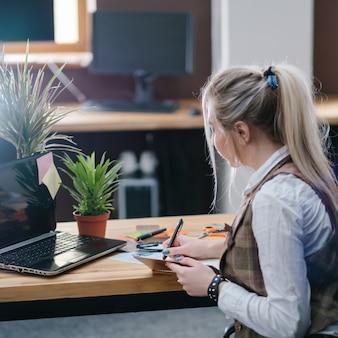 Biurowa przestrzeń robocza. wygodne miejsce pracy. kobieta pracująca w nowoczesnym wnętrzu
