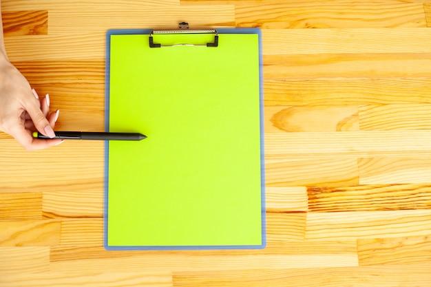 Biurowa ręka trzyma teczkę z papierem w kolorze zielonym na tle drewnianego stołu