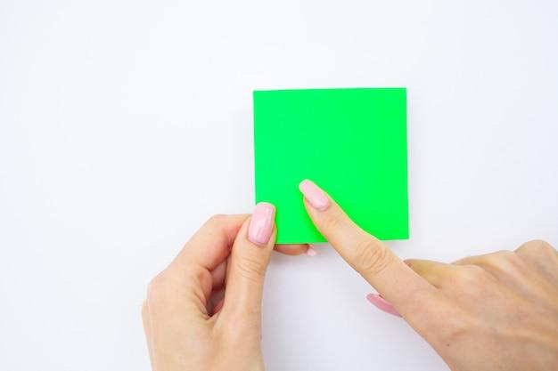 Biurowa ręka trzyma zieloną naklejkę