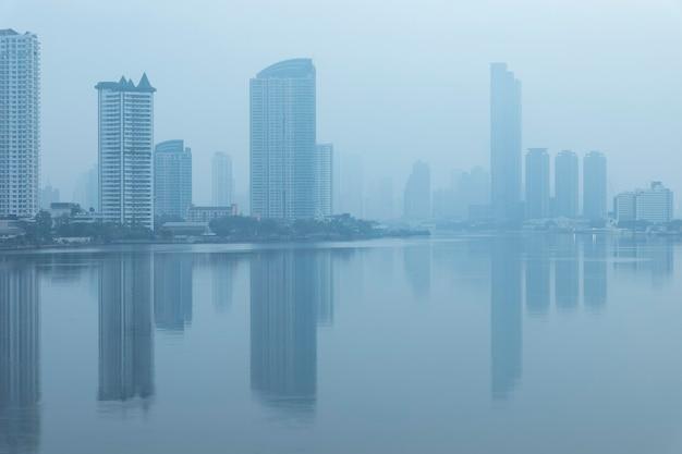 Biurowce i kondominium w bangkoku z rzeką menam i chipami. budynek biurowy pod smogiem w sathorn bangkok. smog pm 2,5 to rodzaj zanieczyszczenia powietrza. bangkok city w zanieczyszczeniu powietrza.
