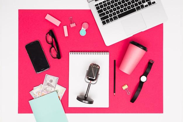 Biurowe miejsce pracy. artykuły biurowe, mikrofon, telefon i laptop oraz pieniądze leżą na różowym stole z ramą