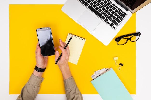 Biurowe miejsce pracy. widok z góry na laptopa, okulary i notebooki z pieniędzmi, rękami z telefonem i makietą na żółtej powierzchni
