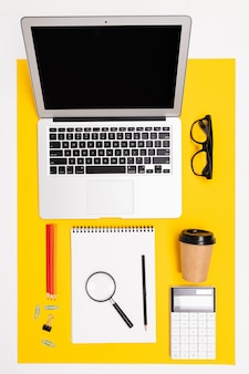 Biurowe miejsce pracy. widok z góry papeterii z laptopem, notatnikami, lupa na żółtej powierzchni