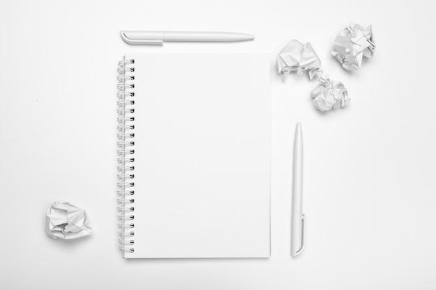 Biurowe miejsce pracy z pustym notatnikiem, zmięty papier