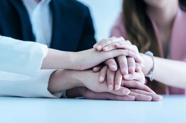 Biurowi ludzie stawia rękę wpólnie dla biznesu sukcesu drużynowego pojęcia