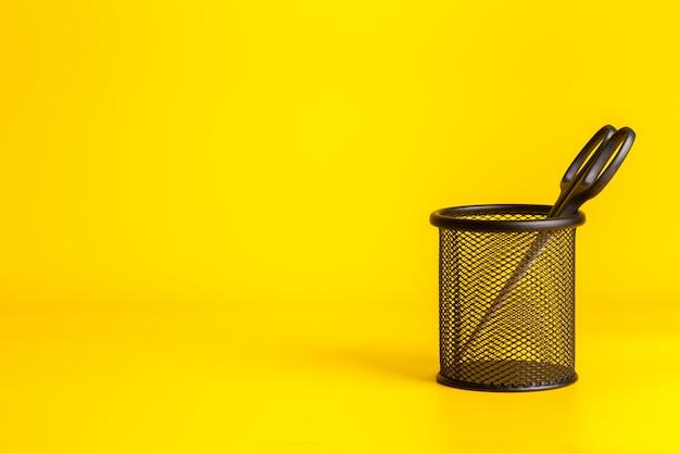 Biurowi narzędziowi nożyce w filiżance na żółtym tle