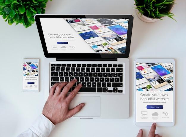 Biurowy blat z tabletem, smartfonem i laptopem pokazujący narzędzie do tworzenia witryn