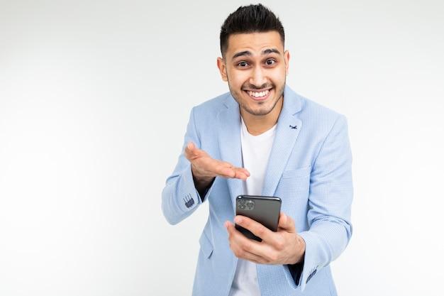Biurowy brunetka mężczyzna w kurtce z uśmiechem wskazuje na ekran gadżetu o dobrej ofercie zakupu na białym tle