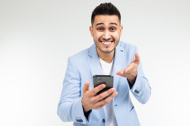 Biurowy brunetka mężczyzna w kurtce z uśmiechem wskazuje na ekran gadżetu o dobrej ofercie zakupu na białym