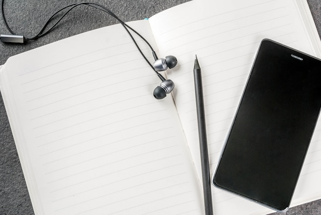 Biurowy, czarny pulpit z urządzeniami. . notatnik, długopisy (ołówki), smartfon i słuchawki na stole.