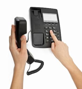 Biurowy czarny telefon z ręką na białym tle