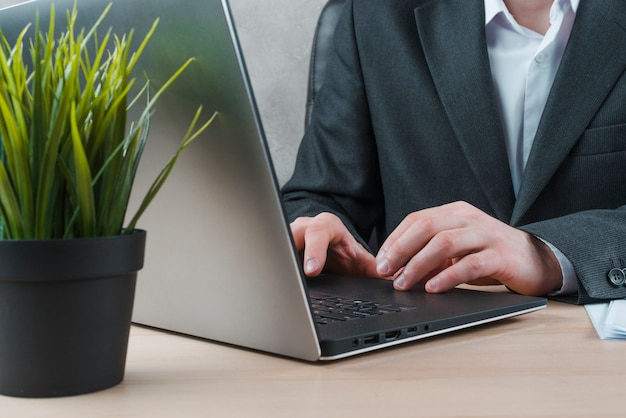 Biurowy desktop z laptopem i biznesowym mężczyzna