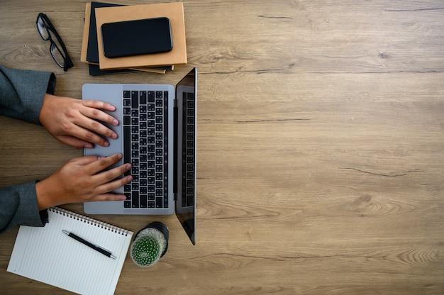 Biurowy komputer stacjonarny laptop mężczyzna wręcza działanie na nowożytnym laptopu odgórnym widoku