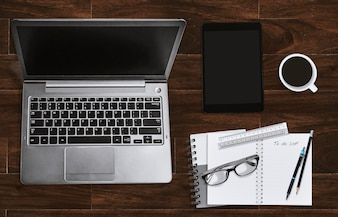 Biurowy miejsce pracy z laptopem i notatnikiem z eyeglasses i pastylką. Widok z góry.
