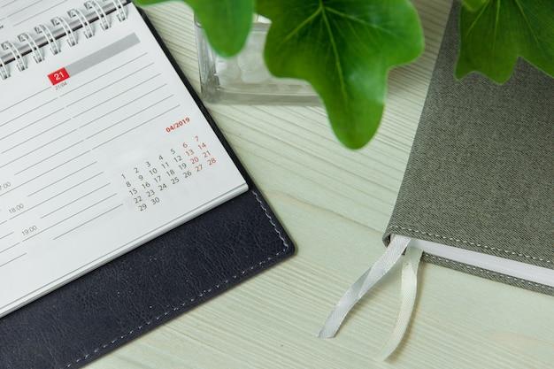 Biurowy miejsce pracy z notatnikiem i garnek rośliny zakończeniem up.