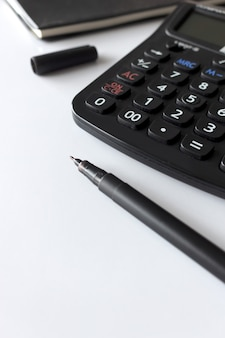 Biurowy miejsce pracy z tekst przestrzenią, czarną książką i kalkulatorem na bielu stole ,.