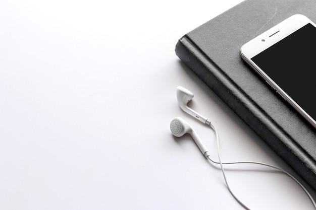 Biurowy miejsce pracy z tekst przestrzenią, czarną książką i smartphone na bielu stole ,.