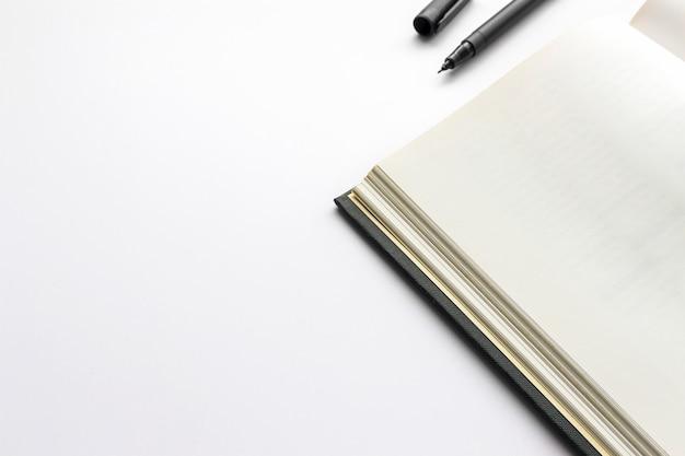 Biurowy miejsce pracy z tekst przestrzenią, otwiera czarną książkę na bielu stole