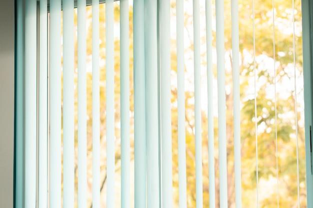 Biurowy okno żaluzi zasłona z natury jesieni koloru widokiem i światło słoneczne w wieczór