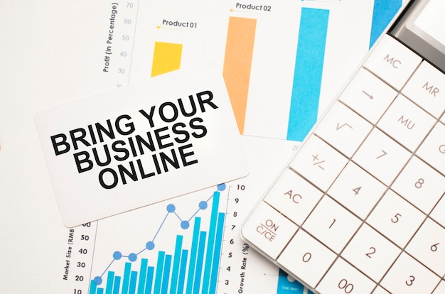 Biurowy stół do pracy z kalkulatorem, wykresami, raportami i tekstem bring your business online na małej kartce na wielobarwnym tle.